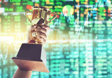 Man holding up a gold trophy cup,win concept. Win concept,Man holding up a gold trophy cup is winner in a competition with stock exchange background stock photography