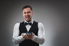 A man holding up poker chips. Poker Stock Image