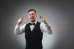A man holding up red poker chips. Poker Royalty Free Stock Photography