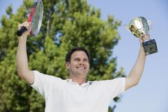 Man Holding up Tennis Rackets and Trophy Stock Image