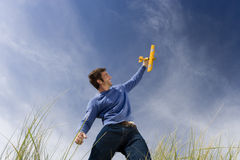Man holding up toy airplane, standing on long grass, low angle view Stock Image