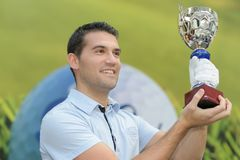 Man holding up trophy cup stock photos