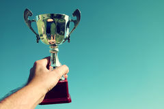 Man holding up a trophy cup as a winner Stock Image