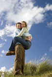 Man holding up woman outdoors, smiling, portrait, low angle view Stock Images
