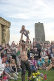 Stonehenge Summer Solstice. Man holding up young child at Stonehenge Wiltshire Summer Solstice celebration royalty free stock image