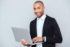 Man holding and using laptop Stock Photos