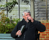 Man holding  a vacuum flask and drinking.. Royalty Free Stock Image
