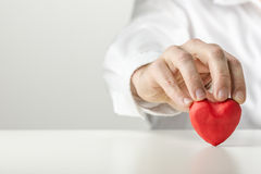 Man holding a Valentine symbolic red heart. Man in a white shirt holding a romantic red heart upright on a counter conceptual of love, romance, Valentines Stock Photo