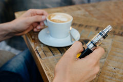 Man holding vape or electronic cigarette and drinking coffee Stock Images