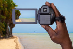 Man holding video camera. Man recording with video camera on a tropical beach Royalty Free Stock Photography