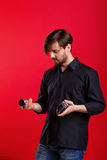 Man holding vintage camera and lens. Photographer lens changes. Hipster in black shirt and jeans Stock Image