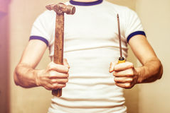 Man holding vintage hammer and screwdriver. Man holding hammer and screwdriver Stock Photos