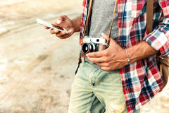 Man holding vintage photo camera and using mobile phone Stock Image