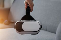 Man holding virtual reality goggles in living room, VR headset Royalty Free Stock Images