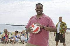 Man Holding Volley Ball At Beach With Friends Grouped Behind Royalty Free Stock Photography
