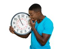 Man holding wall clock, stressed biting fingernails pressured by lack of time Royalty Free Stock Images