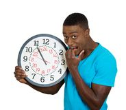 Man holding wall clock, stressed biting fingernails pressured by lack of time Stock Photography