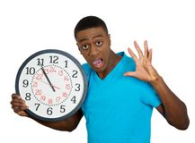 Man holding wall clock, stressed biting fingernails pressured by lack of time Stock Photo