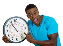 Man holding wall clock, stressed biting fingernails pressured by lack of time Stock Images