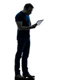 Man holding watching  digital tablet  silhouette. One caucasian man holding watching digital tablet  in silhouette on white background Royalty Free Stock Photo