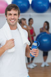 Man holding water bottle with friends in background at fitness studio Royalty Free Stock Photography