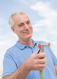 Man Holding Water Hose Against Sky Royalty Free Stock Images