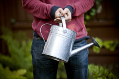 A man holding a watering can Royalty Free Stock Images
