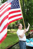 Man holding and waving billowing American flag on dock as he celebrates Independence Day, the Fourth of July. Waving, smiling man holds flag as it blows in wind Stock Images