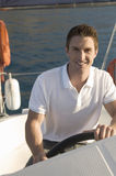 A man holding the wheel of a sailing boat Stock Photo