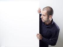 Man holding a white billboard. Portrait of a handsome young man peeping over a blank billboard. Copy-space on a sign or poster. Young man holding a sign Royalty Free Stock Images
