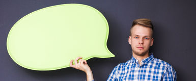 Man holding white blank speech bubble with space for text, Stock Photography