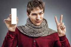 Man holding white box of medicine and shows two fingers. Photo of unhealthy man wrapped scarf. Health care concept Royalty Free Stock Photography