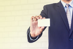 Man holding white business card on concrete. Wall background Royalty Free Stock Photography