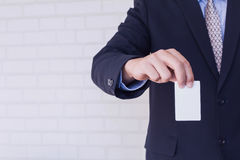 Man holding white business card on concrete. Wall background Stock Images