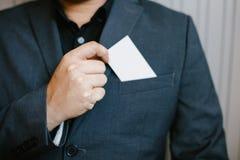 Man holding white business card. Man wearing blue shirt and showing blank white business card. Blurred background. Horizontal mockup, Smart asian business Royalty Free Stock Photos
