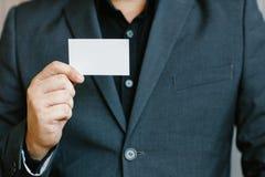 Man holding white business card. Man wearing blue shirt and showing blank white business card. Blurred background. Horizontal mockup, Smart asian business Stock Image
