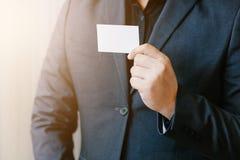 Man holding white business card. Man wearing blue shirt and showing blank white business card. Blurred background. Horizontal mockup, Smart asian business Royalty Free Stock Photography