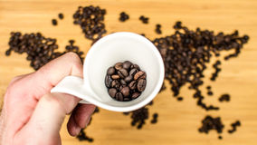 Man is holding white ceramic cup full of coffee beans Royalty Free Stock Image