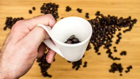 Man is holding white ceramic cup full of coffee beans Stock Image