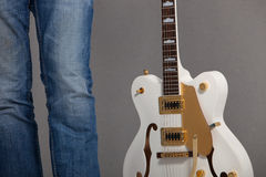 Man holding a white electric guitar. Close-up view of the legs of a man in jeans holding a white electric guitar at his side over a grey background Stock Photo