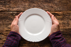 Man holding a white empty plate. On a wooden background Royalty Free Stock Image