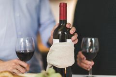 Man Holding White Labeled Red Wine Bottle Near Wine Glasses stock images