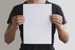 Man holding white A4 paper vertically Stock Photo