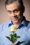 Man holding white rose and smiling. Stock Photo