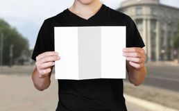 A man holding a white sheet of paper. Holding a booklet. Close up. The background of the city stock image
