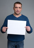 Man holding a white sheet of paper. European-looking male holding a white sheet of paper on a gray background Stock Photo
