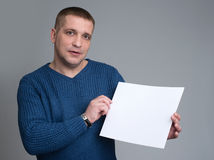 Man holding a white sheet of paper. European-looking male holding a white sheet of paper on a gray background Stock Photography
