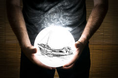 Man Holding White Sphere with a Ship Wreck Inside stock photography