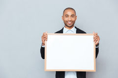Man holding whiteboard. Portrait of smiling african young man holding whiteboard Royalty Free Stock Photo