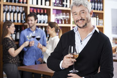 Man Holding Wineglass While Friends Communicating In Shop. Portrait of happy mature men holding wineglass while friends communicating in background at shop Stock Image